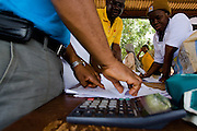 UNICEF staff and local health officials look at results from ongoing vaccination during a national polio immunization exercise in the village of Wantugu, northern Ghana on Friday March 27, 2009..