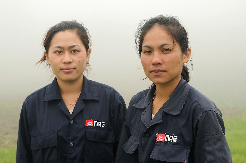 "Mines Advisory Group, Technicians, Sia Thorthongyer, age 19 (left) and Vonekham Dalavong, age 29 (right), take their dangerous jobs seriously, but find humor is sometimes the best way to avoid stress.  They joke about the perils of 12 women trying to share one bathroom in the morning.  Sia said, ""Sometimes we are all standing crossed legged in the que pounding on the door yelling emergency with threats for who ever is in the bathroom.  Sometimes we just run to a bush.""..Laos was part of a ""Secret War"", waged within its borders primarily by the USA and North Vietnam.  Many left over weapons supplied by China and Russia continue to kill.  However, between 90 and 270 million fist size cluster bombs were dropped on Laos by the USA, with a failure rate up to 30%.  Millions of live cluster bombs still contaminate large areas of Laos causing death and injury..The US Military dropped approximately 2 million tons of bombs on Laos making it, per capita, the most heavily bombed country in the world.   ..The women of Mines Advisory Group (MAG) work everyday under dangerous conditions removing unexploded ordinance (UXO) from fields and villages...***All photographs of MAG's work must include (either on the photo or right next to it) the credit as follows:  Mine clearance by MAG (Reg. charity)***."