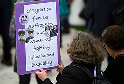 © Licensed to London News Pictures. 24/04/2018. London, UK. A woman holds up a sign at the unveiling of a statue of Millicent Fawcett in Parliament Square, London. Dame Millicent, a leading Suffragist and campaigner for equal rights for women, is the first woman to be commemorated with a statue in Parliament Square. Photo credit: Ben Cawthra/LNP