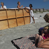 Alyson Lanier and her daughter Be Lanier, 4, watch artists set up an installment during the SARUS Festival Sunday August 24, 2014 at Wrightsville Beach, N.C. (Jason A. Frizzelle)