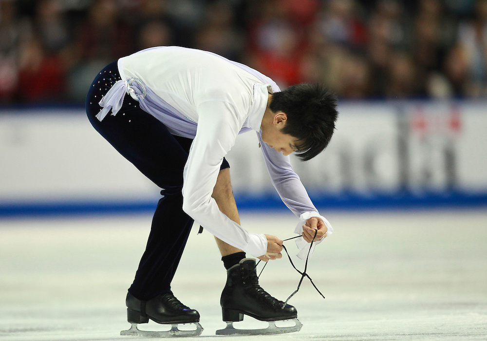 20101030 -- Kingston, Ontario -- Jeremy Ten of Canada ties his skate after the lace broke during his free skate at Skate Canada International in Kingston, Ontario, Canada, October 30, 2010. <br /> AFP PHOTO/Geoff Robins