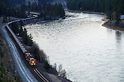 BNSF train with oil tank cars travelling along the Kootenai River. Near Troy in Lincoln County, northwest Montana.