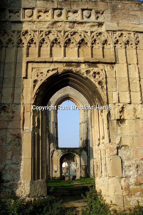 A view through a succession of Gothic arches at the ruins of Crowland Abbey, Lincolnshire, lit by golden early morning sunlight.<br />