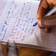 LÉGENDE: Un étudiant prend note. LIEU: CERFER, Lomé, Togo. PERSONNE(S): La main d'un étudiant.