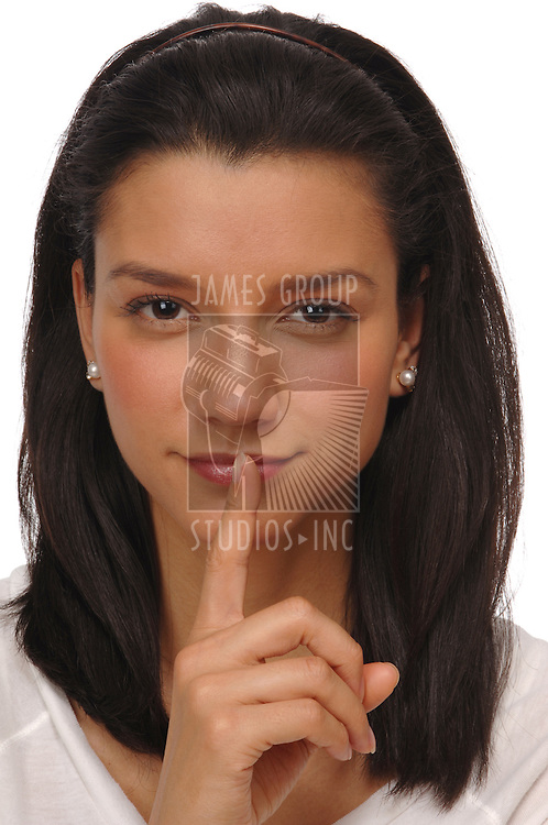 beautiful, young, brunette woman with her index finter over her lips making the shhhhhhhh sign on a white background