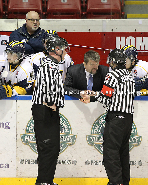 WHITBY, ON - Mar 1, 2015 : Ontario Junior Hockey League game action between the Whitby Fury and the Cobourg Cougars. Game two of the best of seven series. Head Coach Scott McCrory receives an explanation on the call from the Referee in the second period.<br /> (Photo by Tim Bates / OJHL Images)