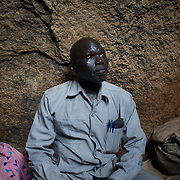 April 28, 2012 - Buram, Nuba Mountains, South Kordofan, Sudan: Mr. Ahmatia, the commissioner of Buram district, visits some families living in the caves of the mountains outside Buram village in South Kordofan's Nuba Mountains...Since the 6th of June 2011, the Sudan's Army Forces (SAF) initiated, under direct orders from President Bashir, an attack campaign against civil areas throughout the South Kordofan's province. Hundreds have been killed and many more injured...Local residents, of Nuba origin, have since lived in fear and the majority moved from their homes to caves in the nearby mountains. Others chose to find refuge in South Sudan, driven by the lack of food cause by the agriculture production halt due to the constant bombardments of rural areas. (Paulo Nunes dos Santos/Polaris)