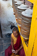 Tibetan Buddhist prayer wheels spin above a Tibetan monk. Bodhnath, Nepal