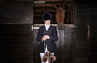 Horse rider with dog and horse at stable