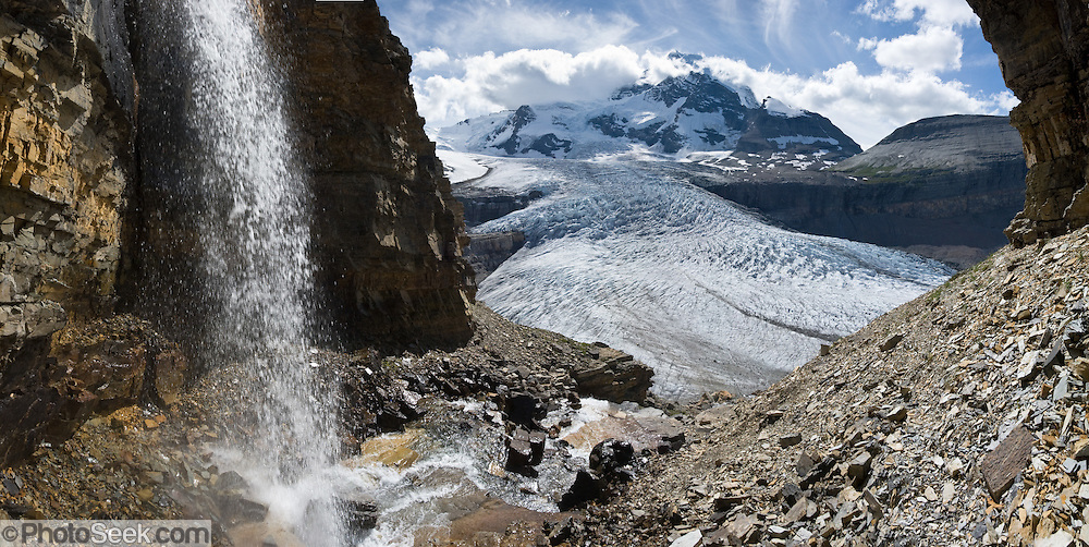 A waterfall flows from Snowbird Pass, above the toe of Robson Glacier in Mount Robson Provincial Park, British Columbia, Canada. Global warming alert: during the past century, Robson Glacier has receded an average of 18 meters per year (1788 meters total from 1911-2010, www.glacierchange.org), and has accelerating melting to 22 meters per year since 1996. An inventory of western Canada glaciers (by Bolch et al 2010) found that from 1985-2005, British Columbia glaciers lost 11% of their area and Alberta glaciers lost 25% of their area. Mount Robson is part of the Canadian Rocky Mountain Parks World Heritage Site declared by UNESCO in 1984. The panorama was stitched from 5 overlapping photos.