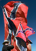 Dennis Mahon holds a small flag as he stands next to a huge 50' x 80' Confederate flag during a pro-Confederate flag rally in Oklahoma City, OK.