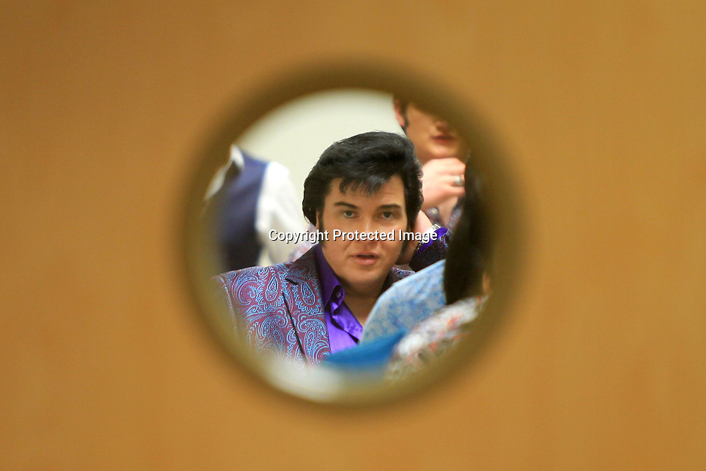 Elvis tribute artist, Jesse Aron, from Green Bay Wisconsin, adjusts his hair before walking into the Birthplace as he and the other 18 tribute artists tour the Elvis Presley Birthplace on Friday afternoon in Tupelo.