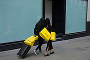 Women Selfridges shoppers seen from behind in Old Bond Street, central London.