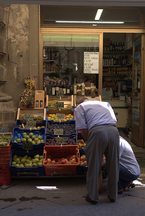 Men shopping at fruit stand in Cortona, Italy