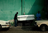 Men carry a coffin out of the morgue at the University Hospital in Port-au-Prince, Haiti, Monday, March 1, 2010. Many of the bodies in the facility are unclaimed from the January 12 earthquake.