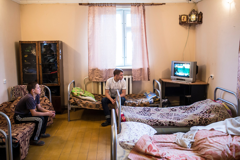 YEKATERINBURG, RUSSIA - OCTOBER 16: Two teenage boys who live at a facility run by City Without Drugs for at-risk youth watch television on October 16, 2013 in Yekaterinburg, Russia. Nine boys, many of whom were either experimenting with drugs or had dropped out of school, live at the group home, where school attendance and homework are mandatory. City Without Drugs is a well-known narcotics treatment program in Russia founded by Yevgeny Roizman, who was elected mayor of Yekaterinburg in September 2013. (Photo by Brendan Hoffman/Getty Images) *** Local Caption ***