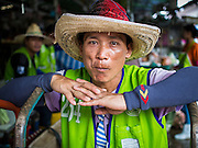 """03 APRIL 2014 - BANGKOK, THAILAND: A porter in Khlong Toey Market waits for customers. People hire porters in the market to carry their purchases out to their cars or waiting taxis. Khlong Toey (also called Khlong Toei) Market is one of the largest """"wet markets"""" in Thailand. The market is located in the midst of one of Bangkok's largest slum areas and close to the city's original deep water port. Thousands of people live in the neighboring slum area. Thousands more shop in the sprawling market for fresh fruits and vegetables as well meat, fish and poultry.     PHOTO BY JACK KURTZ"""