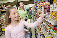 Teenage girl choosing products from supermarket shelf