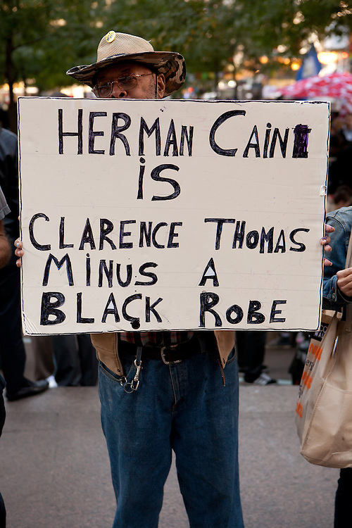 """An African-American man with a sign reading """"Herman Cain is Clarence Thomas minus a black robe."""""""