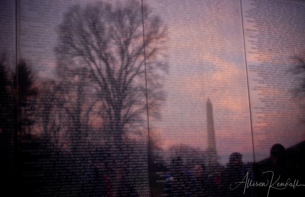 The dark surface of the Vietnam Memorial reflects winter trees and the Washington Monument as a vibrant sunset fills the sky.