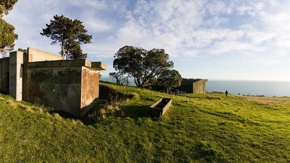 Dramatic sunlight highlights the walls of a gun emplacement and watering trough around Godley Head. A lady walks a dog in the distance.