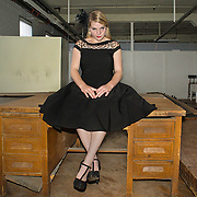 A 17-year-old Caucasian teenager wearing a black 1930s black dress, netted hair piece, and black stilettos, sits on an antique, wooden desk in an old corset factory in Cortland, NY.