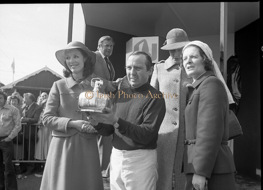 "Irish Distillers Grand National at Fairyhouse.  (M66)..1979..16.04.1979..04.16.1979..16th April 1979..The Irish Distillers Grand National was run today at Fairyhouse Racecourse, Co Meath.The race over 3.5miles is valued at £20,000. the winning trainer will also receive the Tom Dreaper,Perpetual Trophy which will be presented by Mrs Betty Dreaper..Picture of winning owner and rider of ""Tied Cottage"", Mr Anthony Robinson accepting his trophy from Mrs Michael Kennedy,also pictured are, Mrs Dreaper and Mrs Joan Moore, wife of the winning trainer,Mr D L Moore."