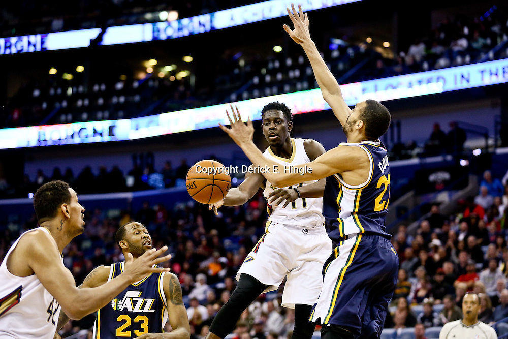 Feb 10, 2016; New Orleans, LA, USA; New Orleans Pelicans guard Jrue Holiday (11) passes to center Alexis Ajinca (42) as Utah Jazz center Rudy Gobert (27) defends during the second quarter of a game at the Smoothie King Center. Mandatory Credit: Derick E. Hingle-USA TODAY Sports