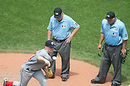 Stephen Strasburg of the Washington Nationals delivers  a practice pitch after the Cleveland grounds crew filled in a hole on the pitcher made during a game against the Cleveland Indians on June 13, 2010 at Progressive Field in Cleveland. Umpires Jerry Crawford, left, and Brian, O'Nora watch on.
