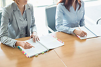 Midsection of businesswomen with books at table in office