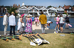 © Licensed to London News Pictures. 04/07/2018. Henley-on-Thames, UK. Family and friends watch as a rowing team leaves the water after a race, on day one of the Henley Royal Regatta, set on the River Thames by the town of Henley-on-Thames in England. Established in 1839, the five day international rowing event, raced over a course of 2,112 meters (1 mile 550 yards), is considered an important part of the English social season. Photo credit: Ben Cawthra/LNP
