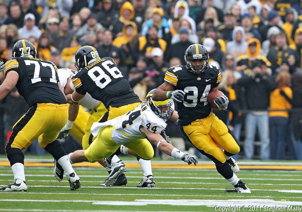 November 05, 2011: Iowa Hawkeyes running back Marcus Coker (34) pulls away from Michigan Wolverines linebacker Desmond Morgan (44) during the second quarter of the NCAA football game between the Michigan Wolverines and the Iowa Hawkeyes at Kinnick Stadium in Iowa City, Iowa on Saturday, November 5, 2011. Iowa defeated Michigan 24-16.