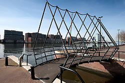 Modern steel footbridge crossing canal in modern Java Island district of Amsterdam Netherlands