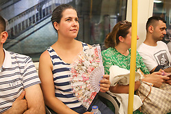 © Licensed to London News Pictures. 25/07/2019. London, UK. Janaina uses a hand held fan to cool down while travelling on Circle Line. According to the Met Office, today will be the hottest day of the year and temperatures are expected to break records. <br /> <br /> ***Permission Granted***<br /> <br /> Photo credit: Dinendra Haria/LNP