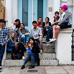 London, UK - 27 August 2012: spectators sit and watch the the annual Notting Hill Carnival parade.