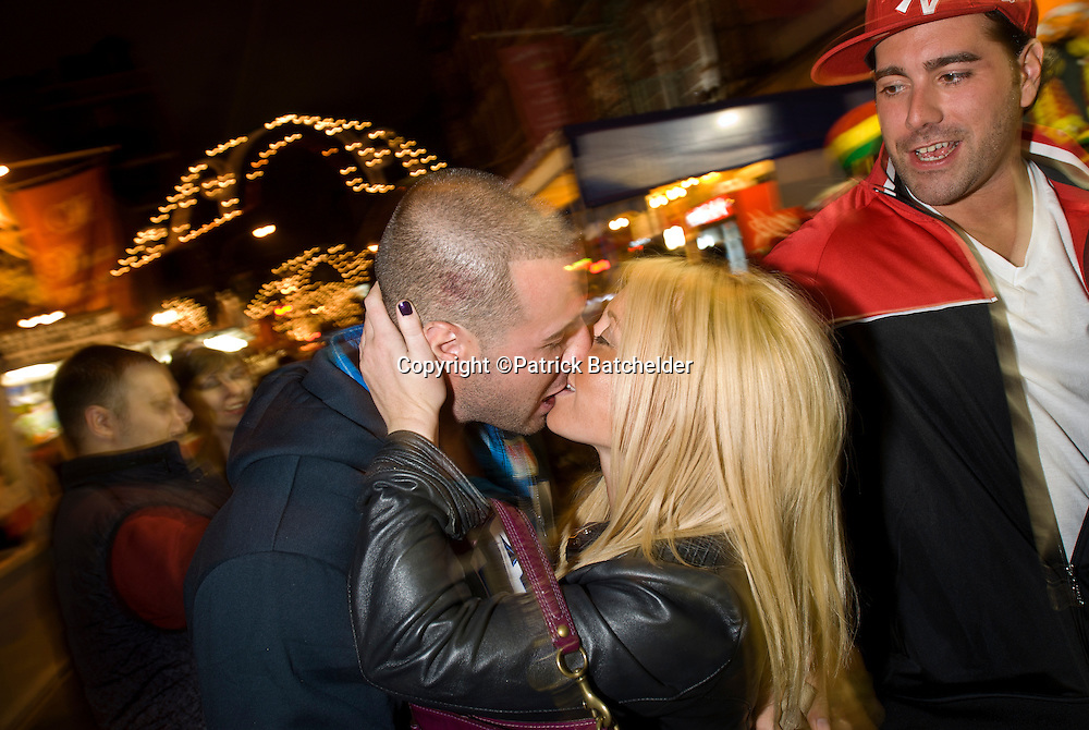 The Feast of San Gennaro in Little Italy, New York City, is a celebration of Italian culture and food held every September. A couple embraces while a friend looks on..