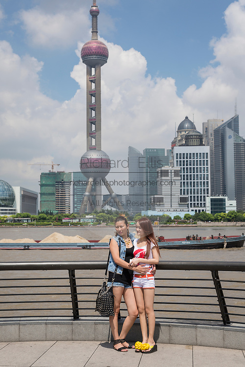 Young women pose for a picture with the skyline of Lujiazui Pudong Shanghai, China