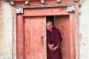 China, Yunnan province, Zhongdian, AKA Shangri-La Songzalin Temple a monk in a door way