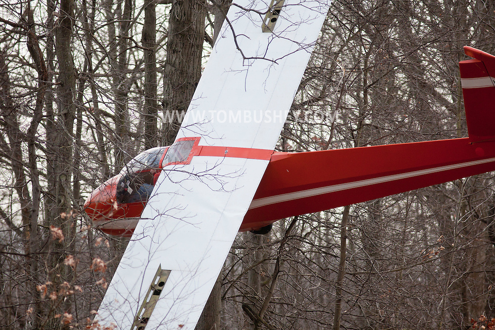 Town of Wallkill, New York - Mechanicstown firefighters work to remove the pilot of a glider that crashed into trees at Randall Airport on Dec. 2, 2012.