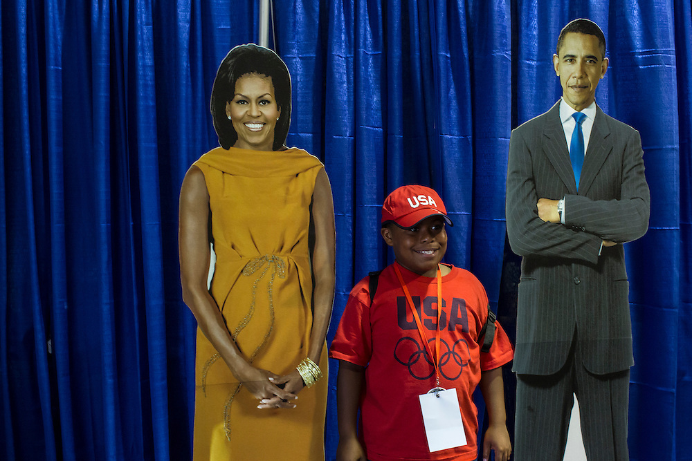 A boy poses for a picture with cardboard cutouts of President Barack Obama and First Lady  Michellle Obama at the American Presidential Experience exhibit on Sunday, September 2, 2012 in Charlotte, NC.