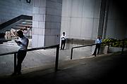 Hong Kong, China - Men smokes and checks his mobile phone on a street in Hong Kong during a work break on April 30, 2018Hong Kong, Chine - Des hommes fument et vérifient leur téléphone portable dans une rue de Hong Kong pendant une pause le 30 avril 2018.