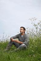 Pensive man sitting in field