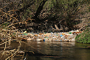 Plastic bottles, tires and other debris is hung up in the Santa Cruz River, which flows with reclaimed water, in the Sonoran Desert at Tubac, Arizona, USA.  The Anza Trail, which parallels the river in this area, is a known route for undocumented migrants who have crossed the border from Mexico.