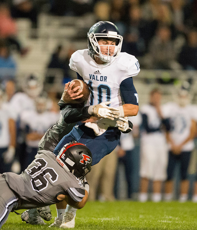 ARVADA - SEPT. 22: Valor Christian's Blake Stenstrom carries the ball through a tackle by Pomona's Michael Allen, left, and Kyle Moretti, obscured at rear, during the first half of a Class 5A nonconference high school varsity football game held at the North Area Athletic Complex. (Photo by Andy Colwell/ Special to The Denver Post)
