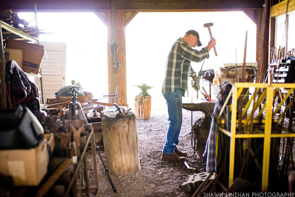 Bob Denman hammers a piece of hot metal to make a Magna Grecia garden tool.
