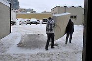 Two men carry a mattress across the snowy parking lot at Worth a Second Look, a second hand store in Kitchener, Ontario, Canada. The two men work under the Job Cafe program of The Working Centre.