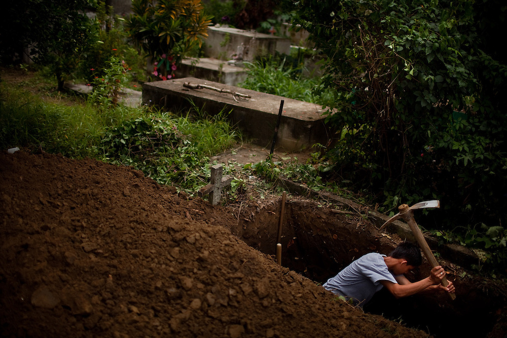 Fernando Ferre, 17, digs the grave for his neighbor Karla Pinto, 23, a mother of three who was killed with two shots in the head in Choloma, a town outside San Pedro de Sula, Honduras, March 11, 2011. The reason for the attack is unclear, but the maras operate in the area and make people pay what is know as Impuesto de Guerra, or War Tax, anyone refusing or failing to pay is executed. Drug trafficking is another problem, and drug related killings are common, as well as robberies and kidnapping. The Hospital Mario Catarino Rivas - San Pedro´s public hospital, attended in 2010 1098 wounded by knife, 1070 wounded by guns and 472 died in the hospital for violent attacks. Photo/Tomas Munita