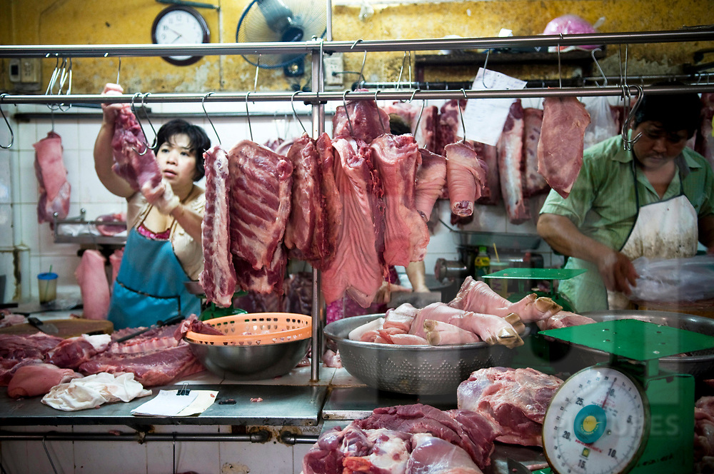 Vietnamese butchers on a market stall in Ho Chi Minh city, Vietnam, Southeast Asia