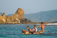 Four playful, laughing boys paddle home from a fishing a outing by late afternoon light, past dramatic sea stacks on the southern coast of Lombok, Indonesia. Travel photography be Djuna Ivereigh.