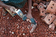 A brick breaker works in a brick yard in Chittagong, Bangladesh. Many buildings need crushed brick for construction, and while machines are available, many people are still employed to complete the process by hand. The gloves they wear are are made from a single piece of rubber, wrapped around each finger and stapled.
